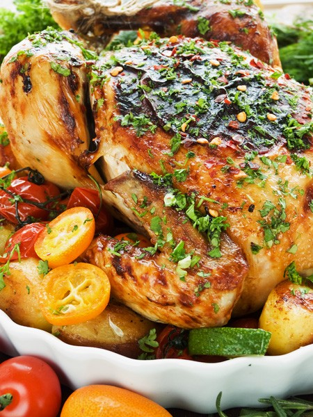 Whole roasted chicken with vegetables herbs and fruits. Shallow dof.