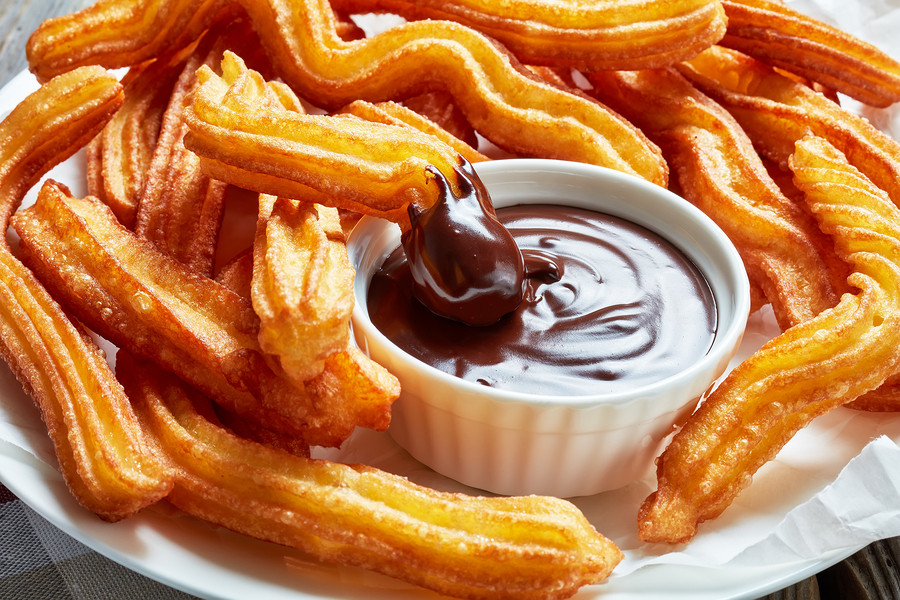 delicious deep fried churros served with chocolate dipping on a white plate on a wooden table with napkin, Traditional spanish and mexican street food, close-up