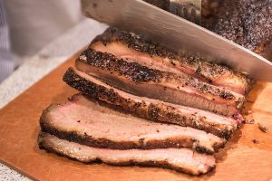 Barbecue beef brisket being cut on cutting board