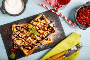 Plate of belgian waffles with chocolate sauce and currant fruit on blue wooden background. From top view.