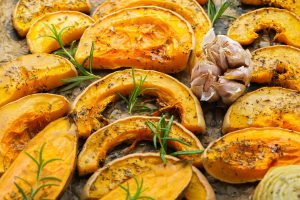 Baked roasted grilled orange pumpkin butternut squash and sweet potato with herbs. Autumn food, soup ingredients. Top view flat lay background