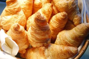 pile of croissant bread on buffet line
