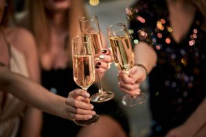 Female Friends Make Toast As They Celebrate At Party. Group Of P