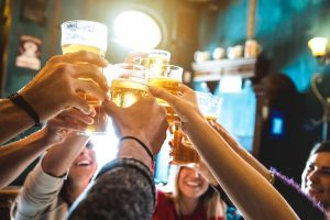 Group Of Happy Friends Drinking And Toasting Beer At Brewery Bar
