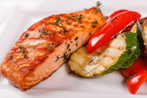 Hot and spicy fillet red fish. Grilled steak salmon or trout with grill paprika and zucchini. Healthy food, seafood and vegetables.