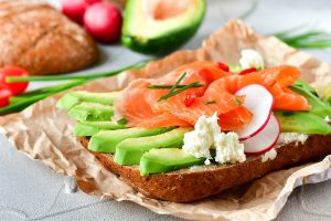 sandwich with avocado and salmon on a light background, green onions and gluten-free grain bread, radishes and tomatoes. concept diet food, copy space, sandwich take away, healthy fast food